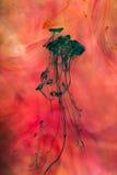 Akrylfärger och färgpulver i vatten Arkivfoton