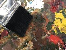 Akrylmålarfärg och borste Arkivfoto