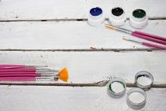 Akrylmålarfärger i asken och borsten som isoleras på vit wood bakgrund arkivfoton