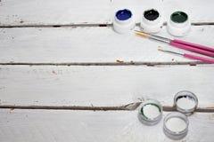 Akrylmålarfärger i asken och borsten som isoleras på vit wood bakgrund royaltyfri bild
