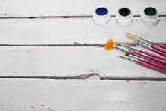 Akrylmålarfärger i asken och borsten som isoleras på vit wood bakgrund arkivbilder