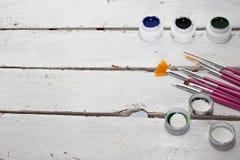 Akrylmålarfärger i asken och borsten som isoleras på vit wood bakgrund royaltyfri fotografi