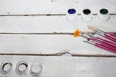 Akrylmålarfärger i asken och borsten som isoleras på vit wood bakgrund arkivbild