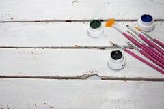 Akrylmålarfärger i asken och borsten som isoleras på vit wood bakgrund royaltyfri foto