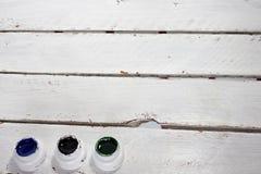 Akrylmålarfärger i asken som isoleras på vit wood bakgrund arkivfoton