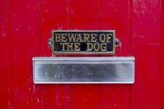 Akta sig av hundtecken på Front Red Door av huset med bokstavsasken för brevbärare Royaltyfri Bild