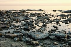 Seascape with flat glass like sea and rocks on the shore at sunset royalty free stock image