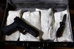 Aktenkoffer mit Drogen und Gewehr Stockfoto