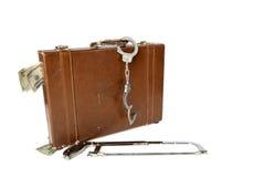 Aktenkofferhandschellen und -säge Stockfotografie