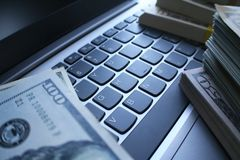 Aktiemarknaden gagnar med buntar av pengar på det högkvalitativa bärbar datortangentbordet Arkivbild