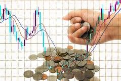 Aktienkurve im Monitor und Hand erhalten Münzen-Investitionskonzept Stockbild