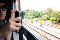 Aktionskamera, die ein Foto der Naturlandschaft durch Fenster des Zugs durch Hände des Touristen macht Lizenzfreies Stockfoto