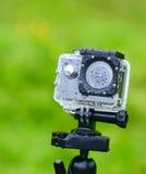 Aktionskamera mit Regen fällt auf grünen Hintergrund im Sommer Stockfotografie