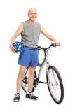 Aktiv äldre man som poserar bredvid en cykel Royaltyfri Bild