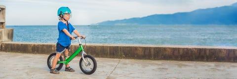 Aktiv blond ungepojke för BANER som kör cykeln i parkera nära havet Litet barnbarn som drömmer och har gyckel på varm sommardag O arkivbilder