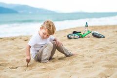 Aktiv blond ungepojke och cykel nära havet Litet barnbarn som drömmer och har gyckel på varm sommardag utomhus lekar för childr Royaltyfri Bild