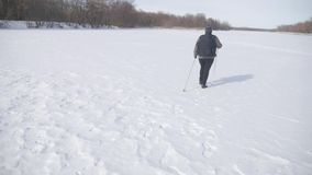 Aktiv eine ?ltere Frau teilgenommen an dem nordischen Gehen mit St?cken im Winterwaldgesunden Lebensstilkonzept f?llig stock video footage