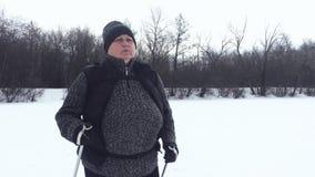 Aktiv eine ?ltere Frau teilgenommen an dem nordischen Gehen mit St?cken im Winterwaldgesunden Lebensstilkonzept f?llig stock video