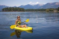 Aktiv färdig kvinna som kayaking på en härlig berg sjö Arkivfoton
