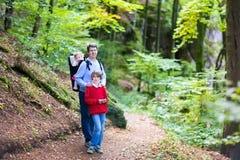 Aktiv fader med ungar som fotvandrar i klippa och skog Arkivbilder