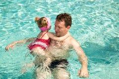 Aktiv fader som undervisar hans barnflicka att simma i pöl Royaltyfri Foto