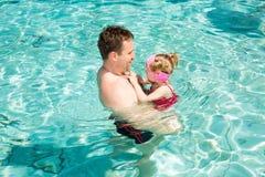 Aktiv fader som undervisar hans barnflicka att simma i pöl Arkivbild