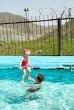 Aktiv fader som undervisar hans barnflicka att simma i pöl Fotografering för Bildbyråer