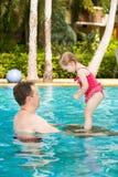 Aktiv fader som undervisar hans litet barndotter att simma i pöl på tropisk semesterort Arkivfoton
