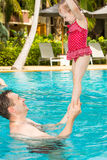 Aktiv fader som undervisar hans litet barndotter att simma i pöl på tropisk semesterort Arkivbilder