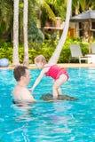 Aktiv fader som undervisar hans litet barndotter att simma i pöl på tropisk semesterort Royaltyfri Foto