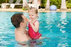 Aktiv fader som undervisar hans litet barndotter att simma i pöl på tropisk semesterort Arkivbild