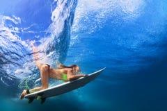 Aktiv flicka i bikini i dykhandling på bränningbräde arkivbilder