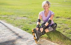 Aktiv hög kvinna som är klar att gå rollerblading Arkivfoto
