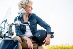 Aktiv hög kvinna som bär ett blått grov bomullstvillomslag, medan sitta på arkivfoton