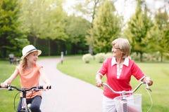 Aktiv hög kvinnaridningcykel i en parkera Royaltyfria Bilder