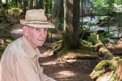 Aktiv hög man som fotvandrar slingaskogen fotografering för bildbyråer