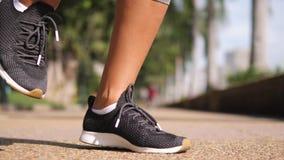 Aktiv idrotts- kvinna som gör benet som värmer upp, innan att köra i morgon Den unga banhoppningen för konditionflickalöpare på s stock video