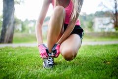 Aktiv jogga kvinnlig löpare som förbereder skor för utbildning Royaltyfri Fotografi