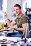 Aktiv kompetent man som sitter på skönhettabellen i studio arkivbilder