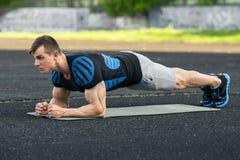 Aktiv konditionman som gör plankövningen i stadion, muskulös manlig genomkörare, utomhus fotografering för bildbyråer