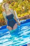 Aktiv kvinna i simbassängen som ser in i avstånd Arkivbild