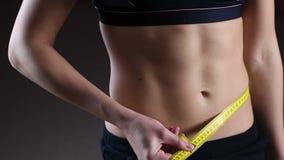 Aktiv kvinna som framlänges visar buken som mäter midjan med bandet, weightloss lager videofilmer