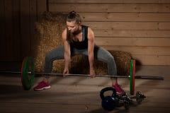 Aktiv kvinnaidrottsman nen som utarbetar med skivstången - powerlifting Arkivfoto