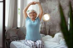 Aktiv kvinnlig som sträcker sig efter ha sovit i sängen royaltyfri foto