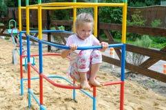 Aktiv liten flicka på sommarlekplats Arkivfoto