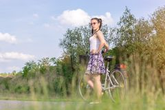 aktiv livstid En kvinna med en cykel tycker om sikten p? sommarskogcykeln och ekologibegreppet arkivfoto