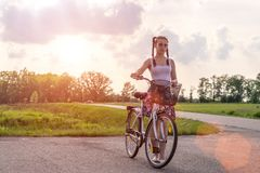 aktiv livstid En ung kvinna med att cykla p? solnedg?ngen i parkerar Cykel och ekologibegrepp royaltyfria foton