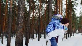 Aktiv mamma som har gyckel med hennes dotter i vinterskogen lager videofilmer