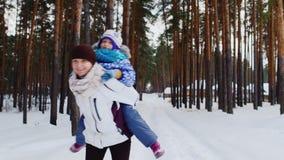 Aktiv mamma som har gyckel med hennes dotter i vinterskogen arkivfilmer