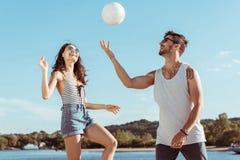 Aktiv man och kvinna som spelar volleyboll på stranden tillsammans Royaltyfri Foto